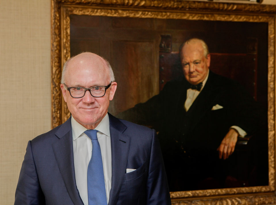 Ambassador Woody Johnson in his new office in the US Embassy, with an inspirational portrait of Sir Winston Churchill. Photo: David Hartnoll, US Embassy, London