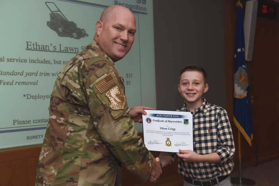 Ethan Grigg presented with a certificate by Col John Stratton