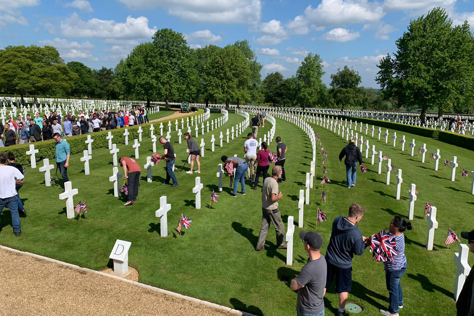 Volunteers dress the headstones at Cambridge American Cemetery